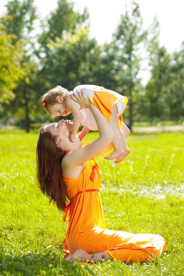 Skönhetmamman och behandla som ett barn utomhus Lycklig familj som spelar i natur Mo arkivfoton