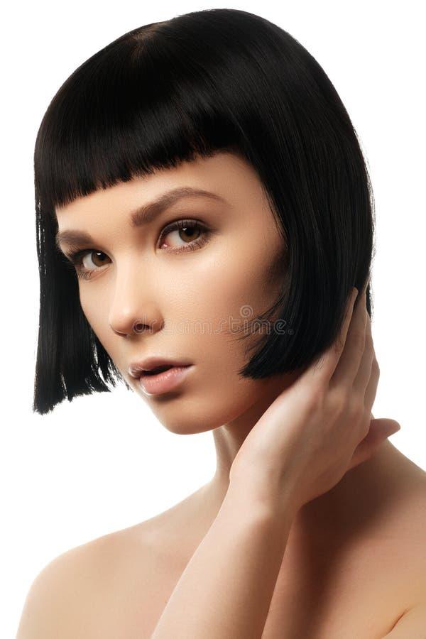 Skönhetmodell med perfekt glansigt svart hår Det lyckliga ung flickainnehav hänger lös på en vitbakgrund royaltyfria bilder