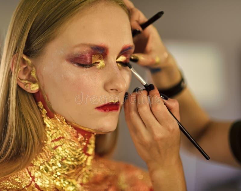 Skönhetmodell som får konstsmink gjort, anlete royaltyfri foto