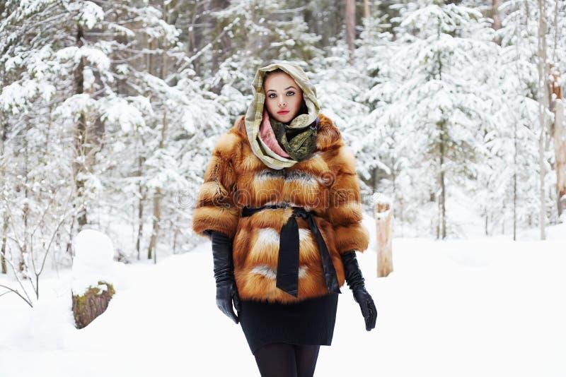 Skönhetmodellflicka i härlig ung kvinna för vinterskog i trendigt pälslag och halsduk arkivfoto