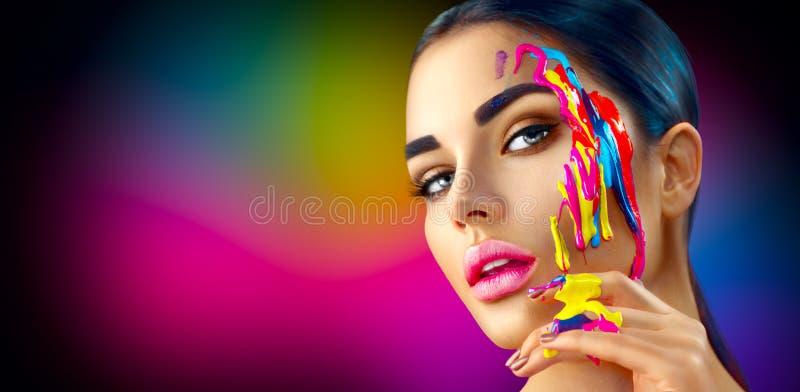 Skönhetmodellflicka med färgrik målarfärg på hennes framsida Härlig kvinna med målarfärg för flödande flytande royaltyfria foton