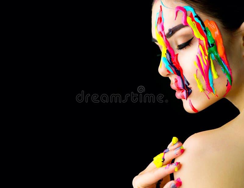 Skönhetmodellflicka med färgrik målarfärg på hennes framsida Stående av den härliga kvinnan med målarfärg för flödande flytande royaltyfri foto