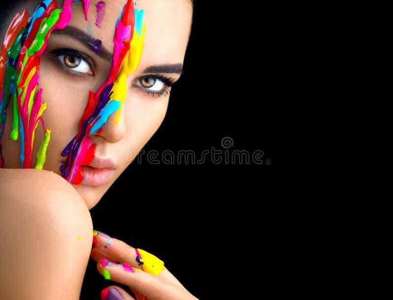 Skönhetmodellflicka med färgrik målarfärg på hennes framsida Stående av den härliga kvinnan med målarfärg för flödande flytande royaltyfri bild