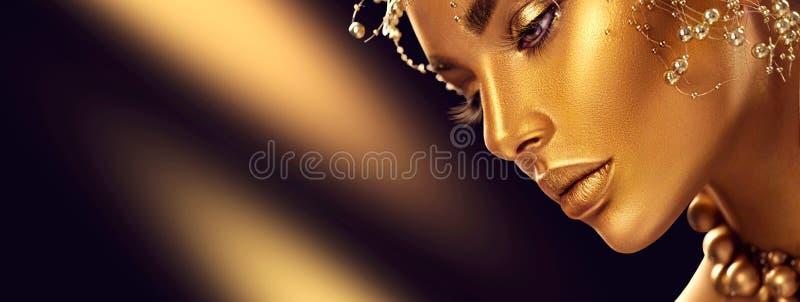 Skönhetmodellflicka med guld- skinande yrkesmässig makeup för ferie Guld- smycken och tillbehör royaltyfria foton