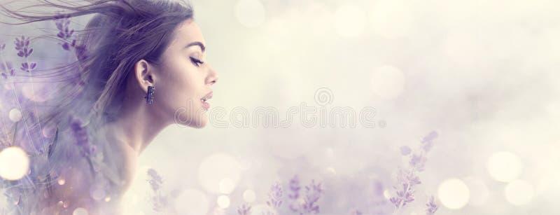 Skönhetmodellflicka med lavendelblommor Härlig ung brunettkvinna med för hårprofil för flyg den långa ståenden fotografering för bildbyråer
