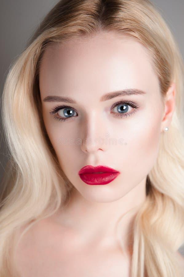 Skönhetmodellflicka med röda kanter för perfekt smink och blåa ögon som ser kameran Stående av den attraktiva unga kvinnan med bl arkivbilder