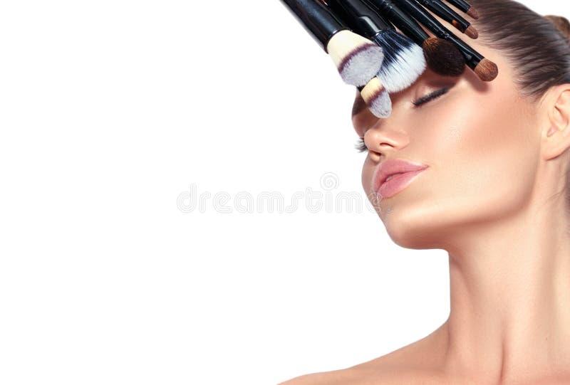 Skönhetmodellflickan, uppsättning för innehav för makeupkonstnär av sminket borstar Ung kvinna för härlig brunett med perfekt hud fotografering för bildbyråer