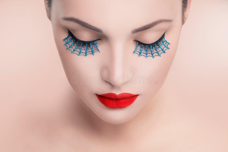 Skönhetmodellkvinna med röda sexiga kanter och blåa falska ögonfrans royaltyfri bild
