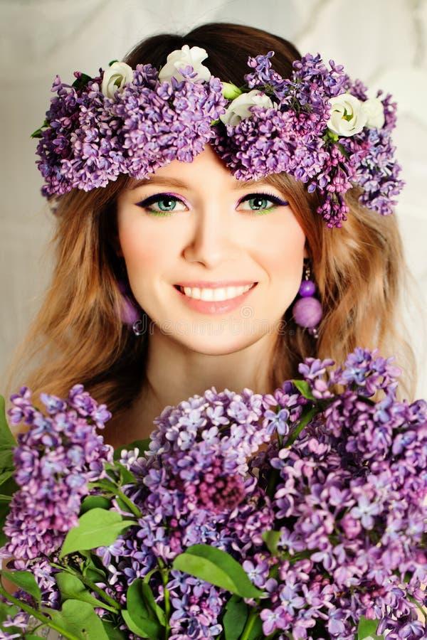 Skönhetmodemodellen Girl med lilan blommar hårstil fotografering för bildbyråer