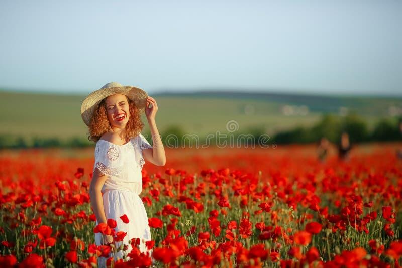 Skönhetmodern med tonårigt tycker om sommardagar Gullig utsmyckad klädd flicka i vallmofält Fält av blommande vallmo arkivfoton