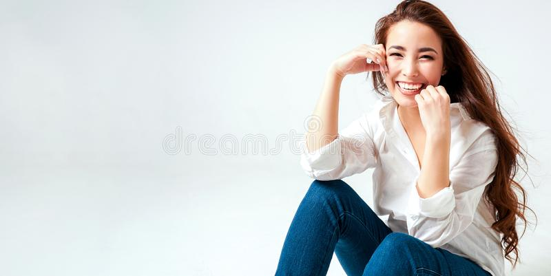 Skönhetmodestående av att le den sinnliga asiatiska unga kvinnan med mörkt långt hår i den vita skjortan på det vita bakgrundsban arkivfoton
