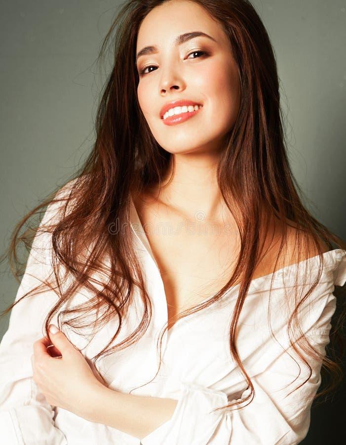 Skönhetmodestående av att le den sinnliga asiatiska unga kvinnan med mörkt långt hår i den vita skjortan på grå bakgrund arkivfoton