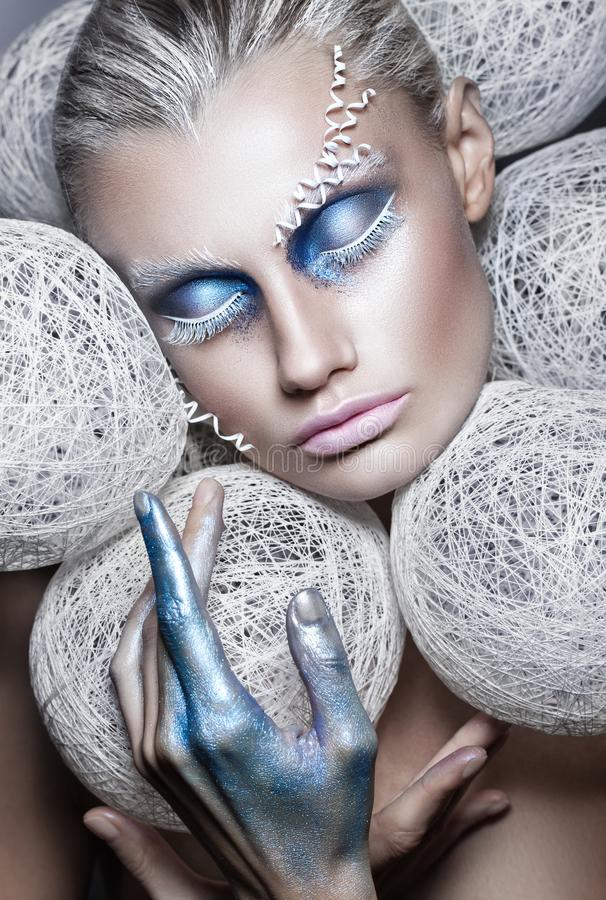 Skönhetmodestående av den härliga kvinnan med vita bollar för idérikt smink runt om huvudmodellen makeover i blått och vitt arkivbilder