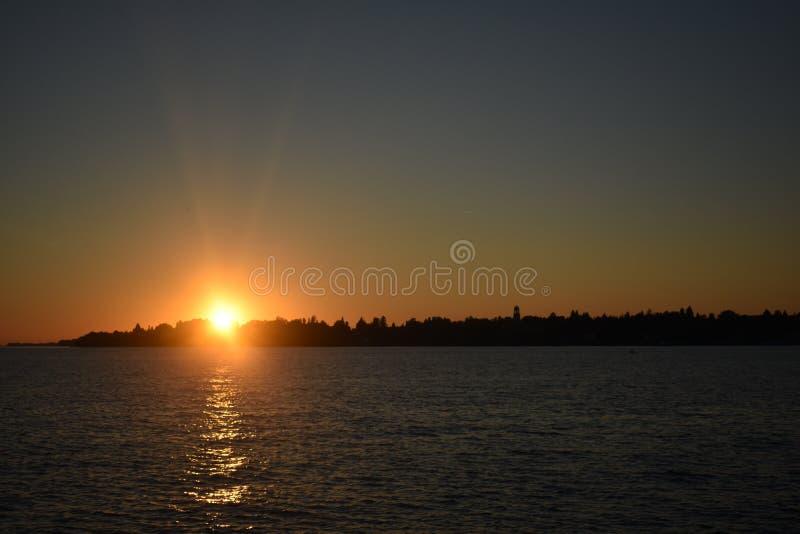 Skönhetnatursolnedgång med sjön fotografering för bildbyråer