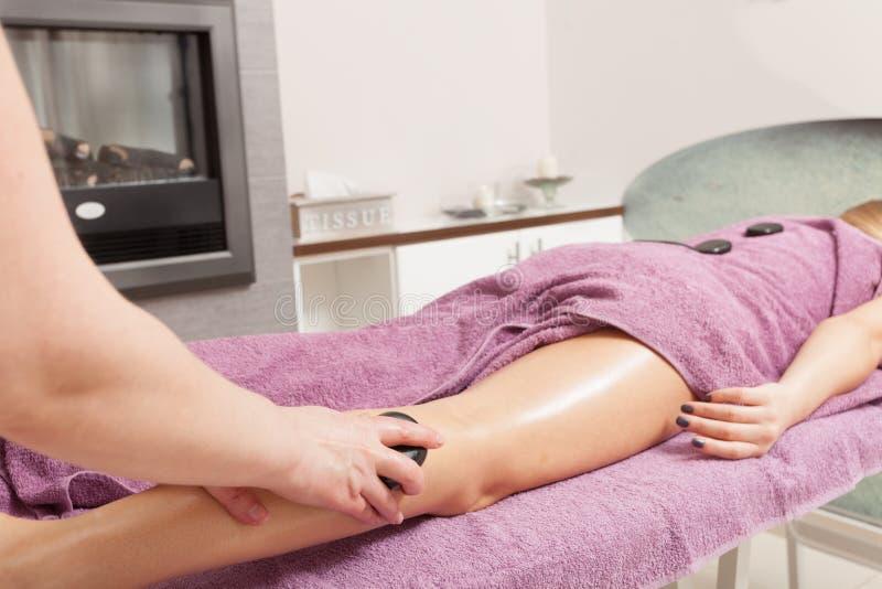 Skönhetsalong. Kvinna som får brunnsort varm stenbenmassage arkivbild