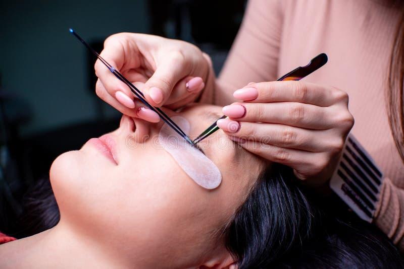 Skönhetsalong, slut för ögonfransförlängningstillvägagångssätt upp lång kvinna för härligt hår royaltyfria bilder