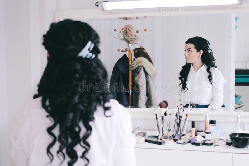 Skönhetsalongen, flicka med långt svart hår sitter på spegeln i skönhetstudion arkivfoton