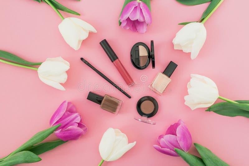 Skönhetsammansättning med tulpanblommor och skönhetsmedel på rosa bakgrund Top beskådar Lekmanna- lägenhet arkivfoto
