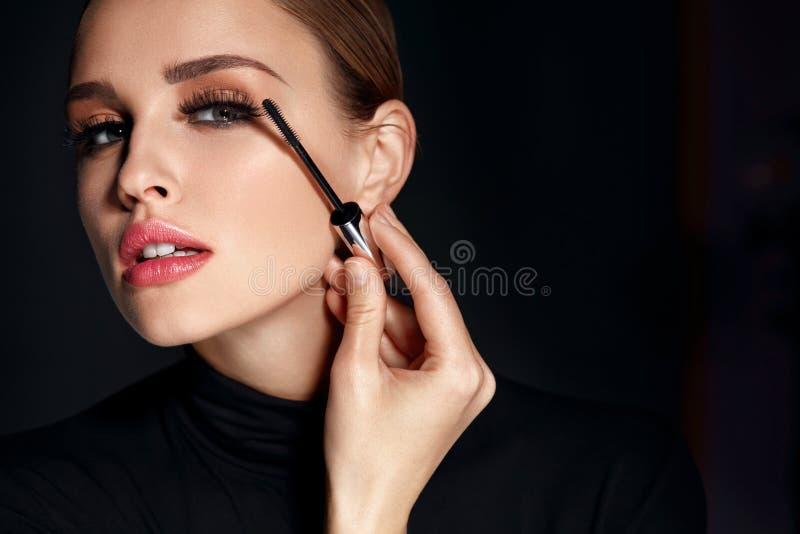 Skönhetskönhetsmedel Kvinna som sätter svart mascara på långa ögonfrans royaltyfria foton