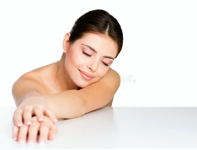 Skönhetskottet av en ung modell som trycker på hennes händer med ögon, stängde sig royaltyfri foto