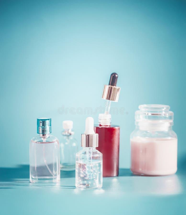 Skönhetsmedel i flaskbehållare Inställning för hudomsorg med färgpulver, extrakt, serum och kräm på turkosblåttbakgrund, främre s arkivbilder