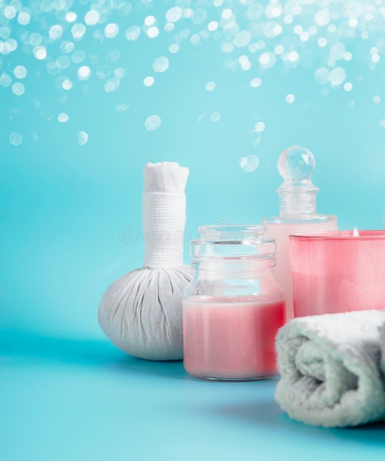 Skönhetsmedel med handduk- och massagestämpeln för brunnsortbehandling på ljust - blå bakgrund med bokeh royaltyfri fotografi