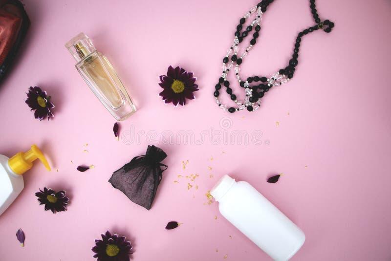 Skönhetsmedel på tabellen på kvinnan Kosmetisk påse, skönhetsmedel och hygienprodukter Rosa bakgrund för text arkivfoton