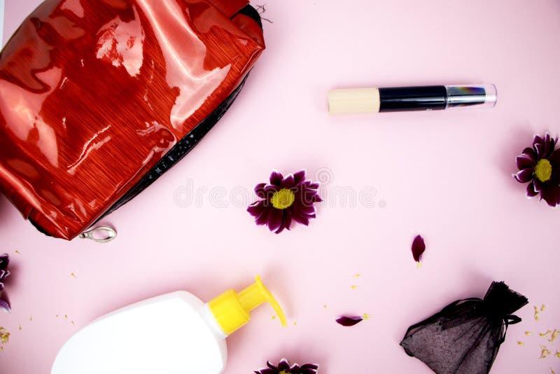 Skönhetsmedel på tabellen på kvinnan Kosmetisk påse, skönhetsmedel och hygienprodukter Rosa bakgrund för text royaltyfri foto