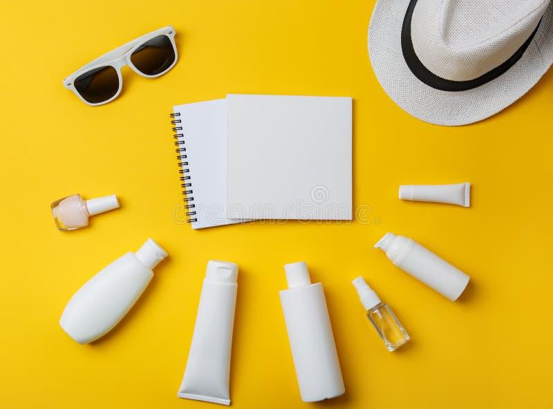 Skönhetsmedel, Panama och solglasögon för sommarhudomsorg på gul bakgrund arkivfoto