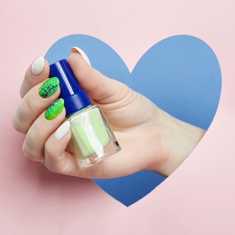 Skönhetsmedel räcker makeup som är härlig spikar manikyr, spikar polermedel som annonserar på kulör pappers- bakgrund Fingrar med arkivfoton