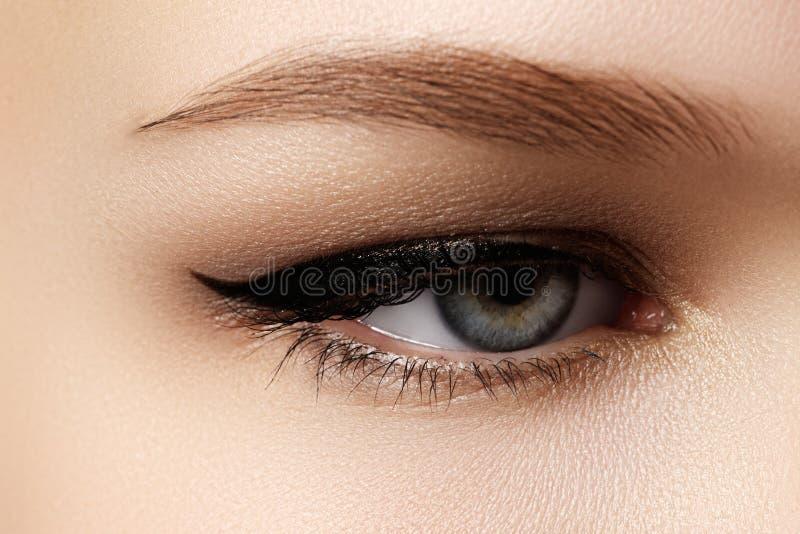 Skönhetsmedel & smink Härligt kvinnligt öga med den sexiga svarta eyeliner royaltyfri foto