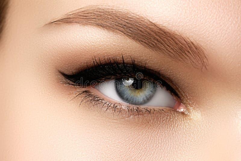Skönhetsmedel & smink Härligt kvinnligt öga med den sexiga svarta eyeliner royaltyfri bild