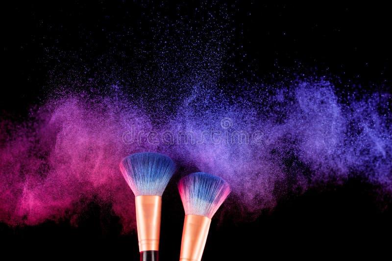 Skönhetsmedelborste och färgrikt makeuppulver för explosion royaltyfri foto