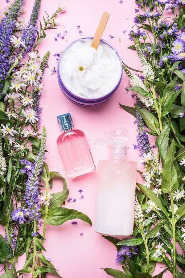 Skönhetsmedlet buteljerar och skorrar behållare med gröna örter och blommor på rosa bakgrund, bästa sikt Tom etikett för att brän royaltyfria foton