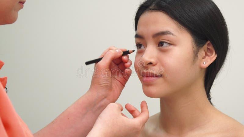 Skönhetspecialisten använder den kosmetiska blyertspennan royaltyfria foton