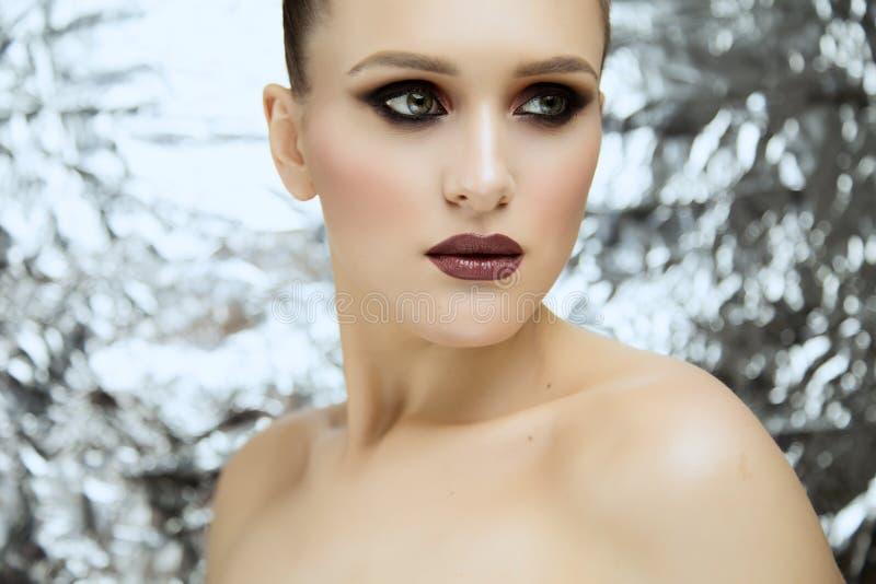 Skönhetstående av bärande makeup för ung attraktiv flicka i studio fotografering för bildbyråer