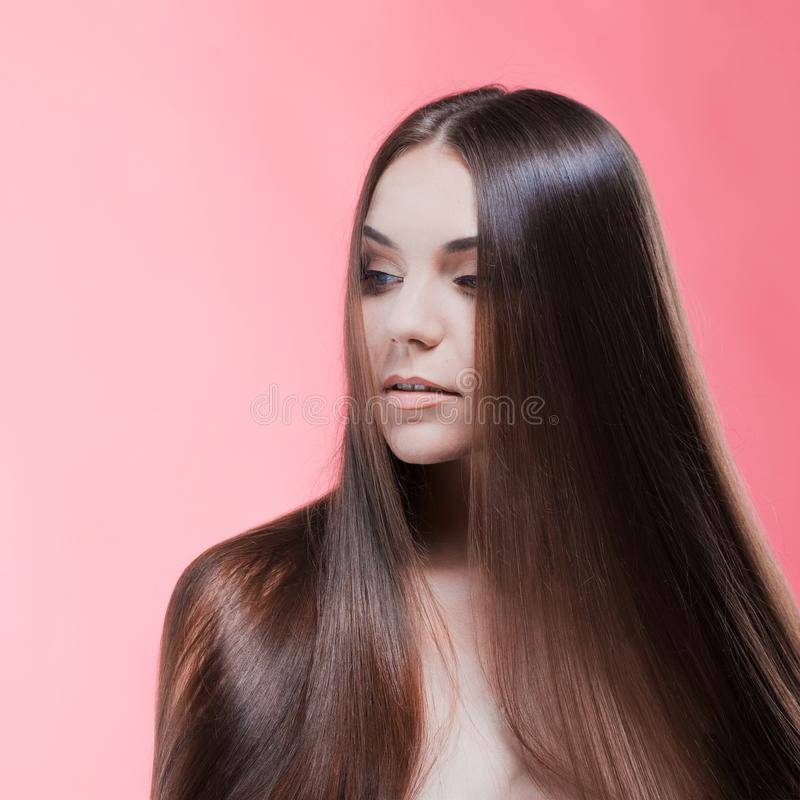 Skönhetstående av brunetten med perfekt hår, på en rosa bakgrund Den unga asiatiska flickan som kammar hår med, fingrar isolerat  royaltyfri bild