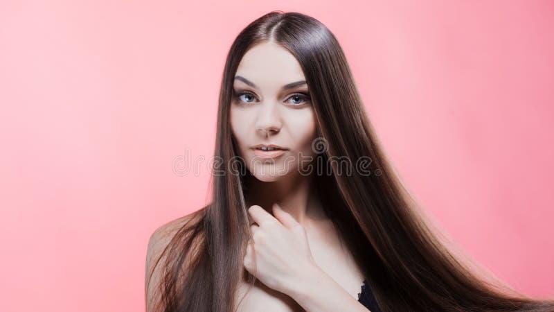 Skönhetstående av brunetten med perfekt hår, på en rosa bakgrund Den unga asiatiska flickan som kammar hår med, fingrar isolerat  royaltyfria bilder