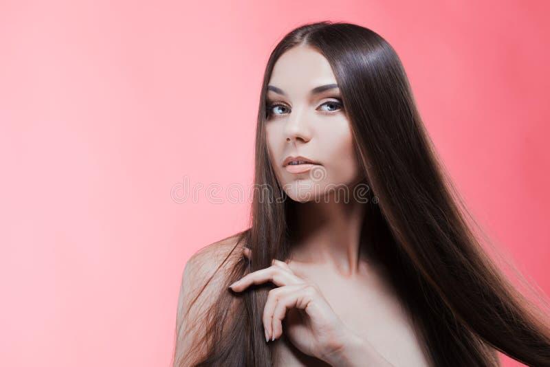 Skönhetstående av brunetten med perfekt hår, på en rosa bakgrund Den unga asiatiska flickan som kammar hår med, fingrar isolerat  royaltyfri fotografi