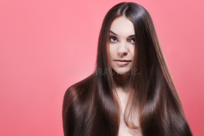 Skönhetstående av brunetten med perfekt hår, på en rosa bakgrund Den unga asiatiska flickan som kammar hår med, fingrar isolerat  arkivbilder