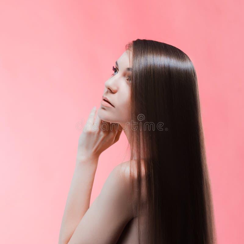 Skönhetstående av brunetten med perfekt hår, på en rosa bakgrund Den unga asiatiska flickan som kammar hår med, fingrar isolerat  arkivfoto
