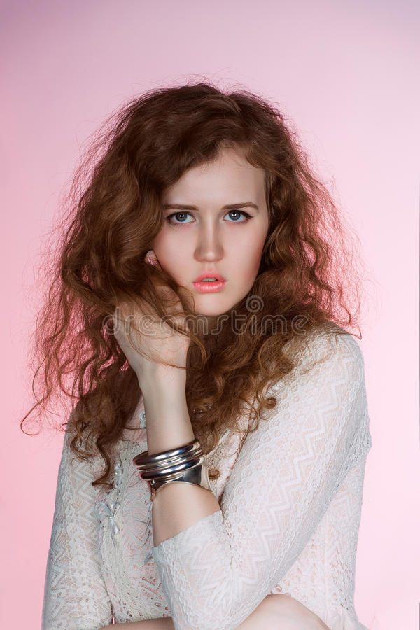 Skönhetstående av brunettkvinnan med långt krabbt hår som isoleras på rosa bakgrund fashion smycken Klipp modellen Woman perfekt  royaltyfria foton
