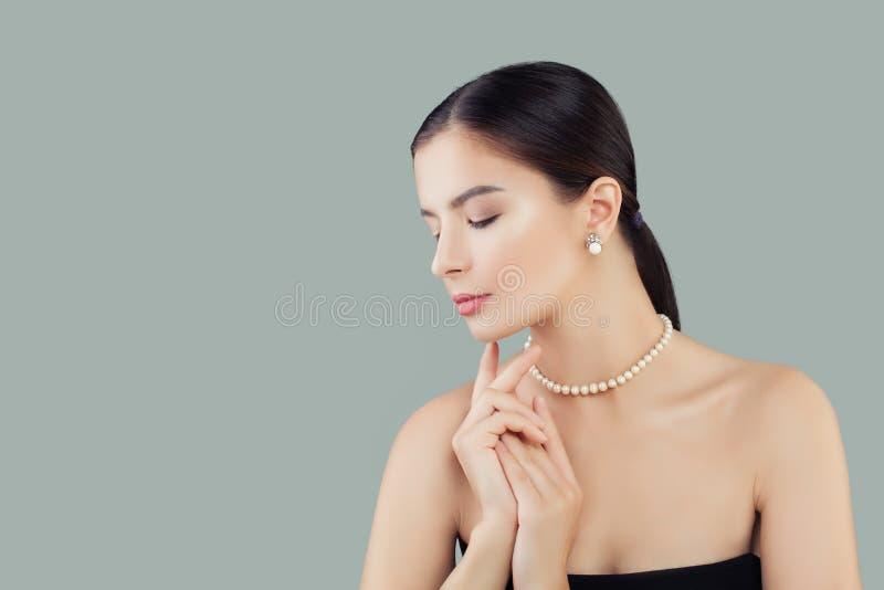 Skönhetstående av den eleganta modellkvinnan i pärlor halsband och örhängen royaltyfri foto