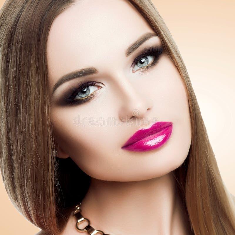 Skönhetstående av den härliga damen med ljus makeup, guld, ljusa fuchsiakanter Skönhet mode som ansar stilfullt royaltyfri foto
