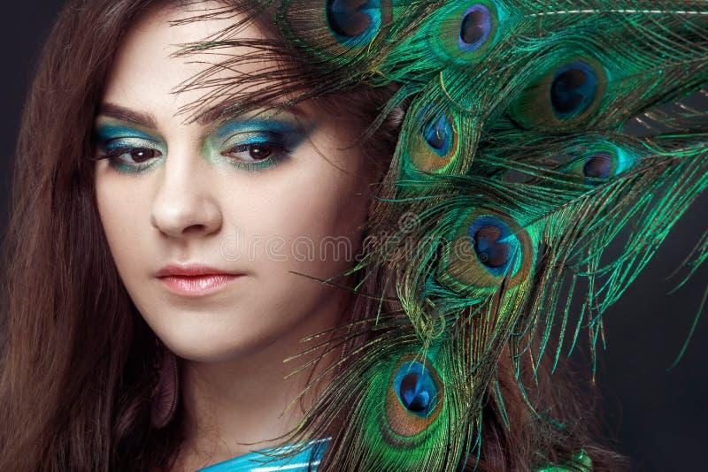 Skönhetstående av den härliga flickan som täcker ögonen med påfågelfjädern Idérika makeuppeafowlfjädrar _ royaltyfria foton
