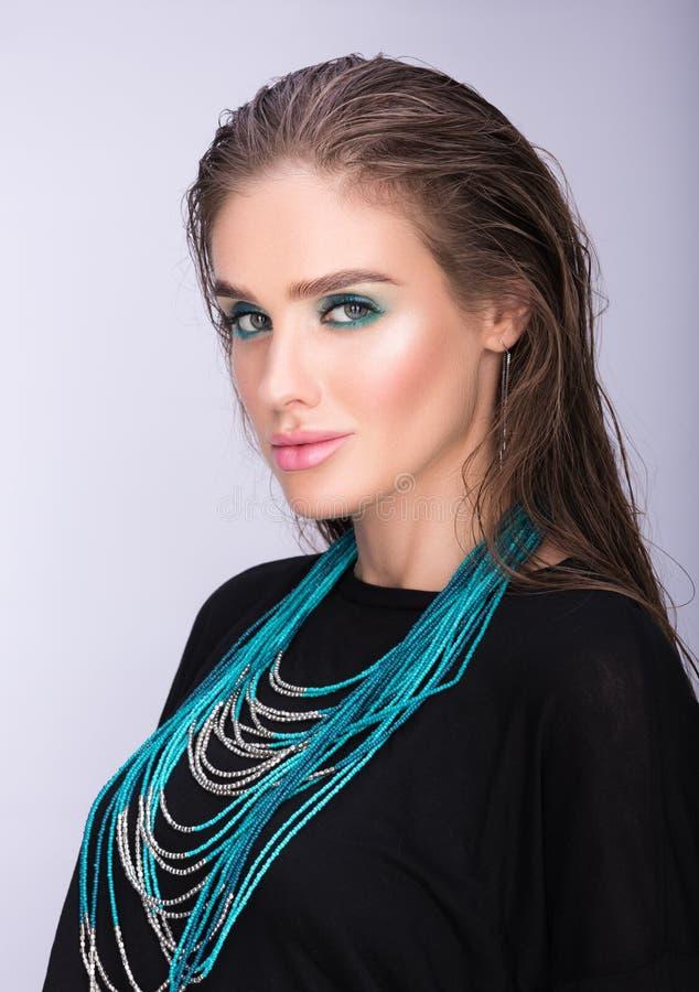 Skönhetstående av den härliga unga kvinnan med våt hår- och professionellmakeup fotografering för bildbyråer