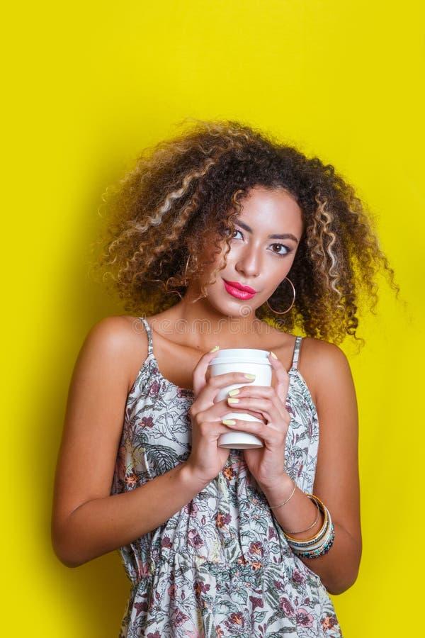 Skönhetstående av den unga afrikansk amerikankvinnan med den afro frisyren Flickan som poserar med kaffe på gul bakgrund som ser, royaltyfri foto