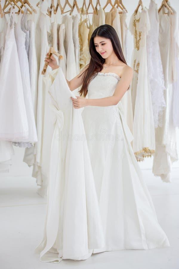 Skönhetstående av den unga asiatiska bruden som väljer bröllopsklänningen, i att gifta sig salongen av modelagret som är lyxig arkivfoto