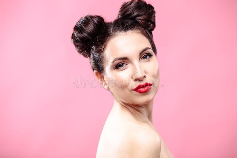 Skönhetstående av den unga brunettkvinnan på en ljus rosa bakgrund Modell med smink och frisyren royaltyfri fotografi