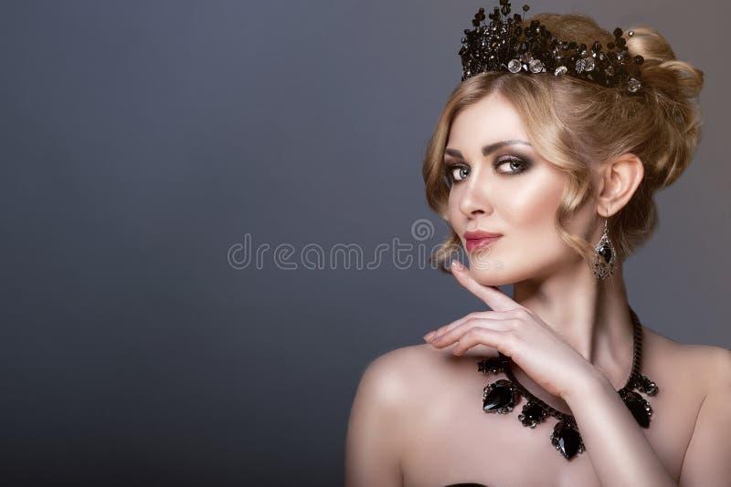 Skönhetstående av den ursnygga unga blonda modellen som bär den svarta juvelkronan och uppsättningen av lyxig halsband och örhäng royaltyfri fotografi